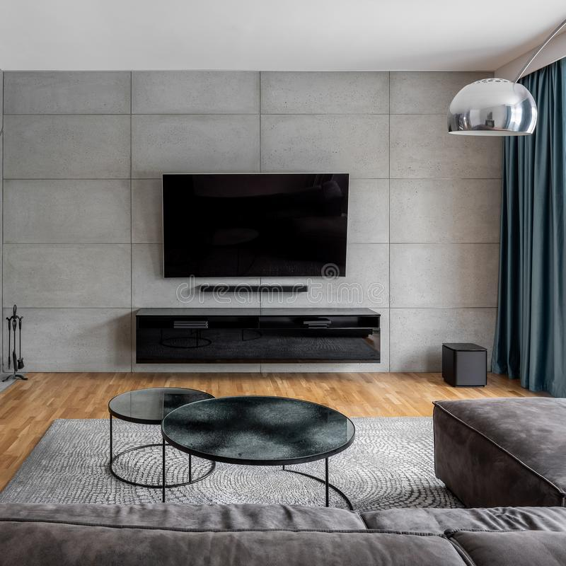 Living room with cement wall. Living room with gray cement wall and wall mounted tv royalty free stock images