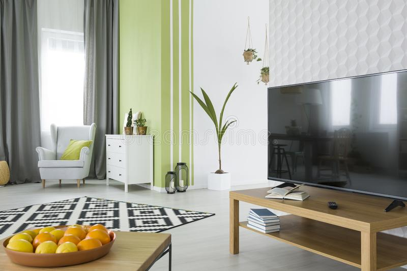 Living room with 3d wallpaper. Living room with white 3d wallpaper, tv, dresser and armchair royalty free stock photo