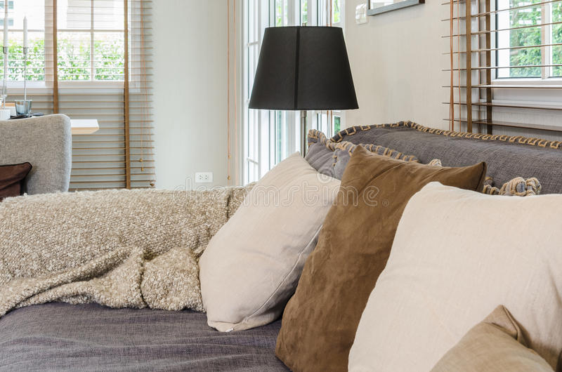Living room design with pillows on grey sofa and black lamp royalty free stock photos