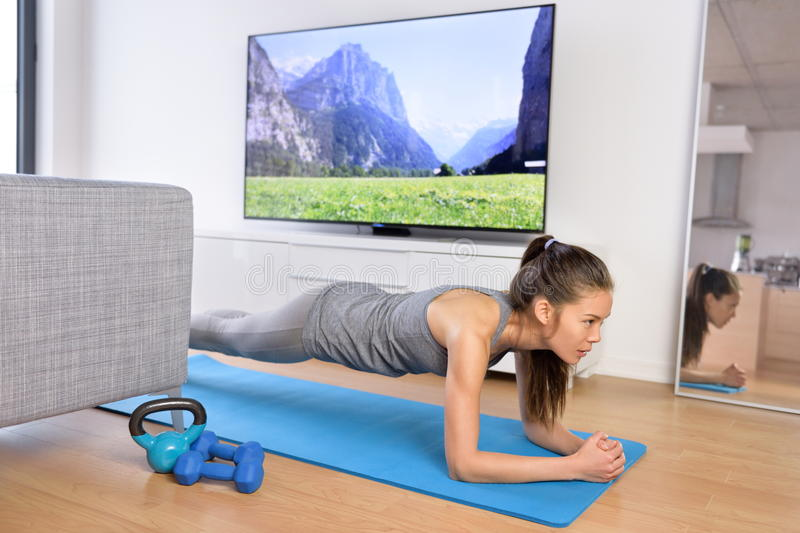 Living room exercises - girl doing plank at home royalty free stock photography