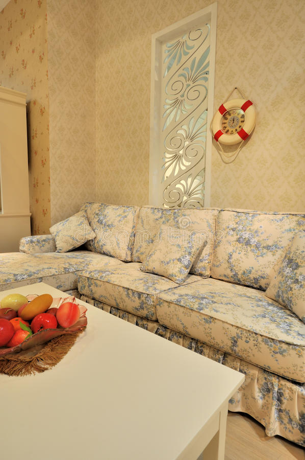 Living room with flowery sofa. Blue flowery and comfortable cloth sofa in living room with ornaments and decoration royalty free stock photos