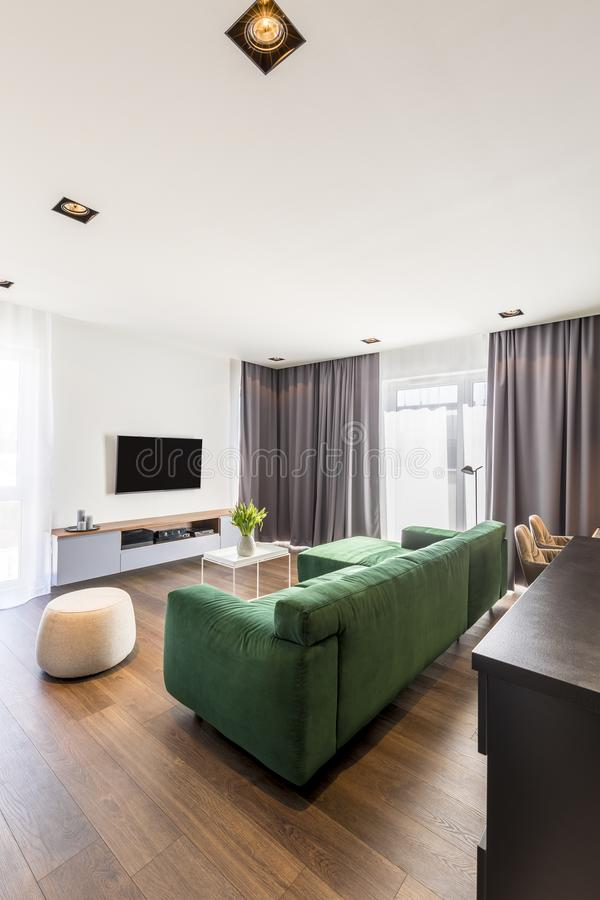 Living room with green sofa. Spacious living room interior with green corner sofa, wooden floor, gray drapes and TV set stock photos