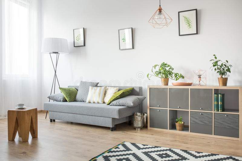 Living room with grey couch. Bookcase and wooden side table royalty free stock photography