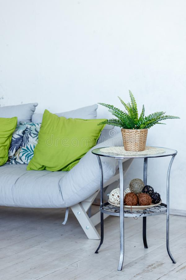 Living room with grey sofa, decorative green pillows and plant.Stylish Interior of room in eco style with soft couch and royalty free stock photography