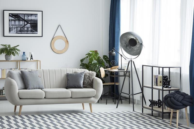Living room with industrial lamp. Industrial lamp next to beige settee in living room interior with patterned carpet and poster royalty free stock photography