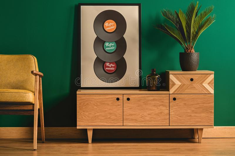 Poster with vinyl. Living room interior with creative poster with vinyl on a wooden cabinet next to a plant royalty free stock images