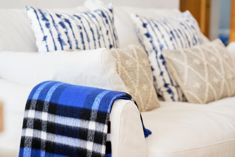 Living room interior with fabric material white colour sofa blue beige elements cushions and plaid close up image stock photos