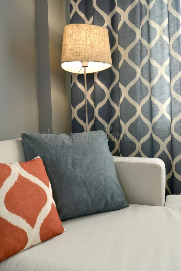 Living room interior fragment with a floor lamp and throw pillows.  royalty free stock images