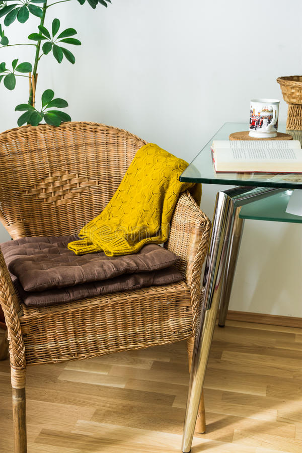 Living room interior woven rattan chair, cushions, knitted sweater, open book, tea cup, green potted plant, cozy atmosphere royalty free stock images