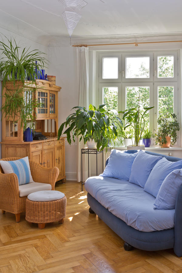 Living room in old building. Bright living room in old building with stucco, sofa, armchair, stool and antique cupboard in blue and warm colors stock photography