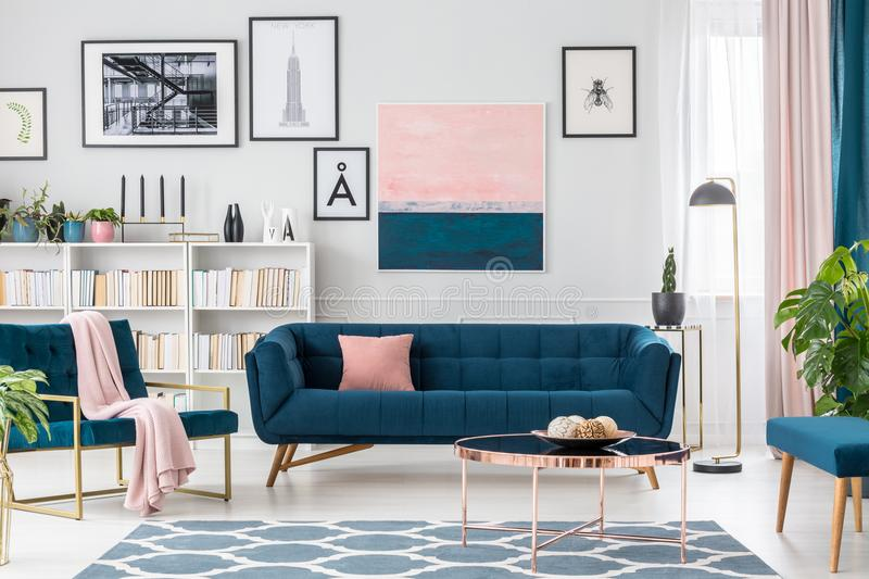 Living room with pink details. Modern living room interior with blue sofa, rug, art collection and pink details royalty free stock images