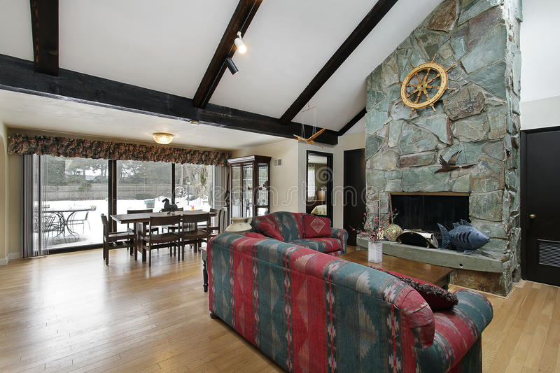 Living room with stone fireplace. Living room with dining area and stone fireplace stock images