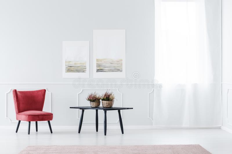 Living room with wall molding. Red, velvet armchair in bright living room interior with black table and wall with molding royalty free stock images