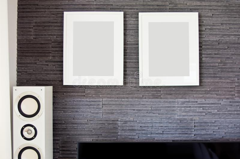Living room wall with two empty frames and loudspeaker. Horizontal gray granite slates wall texture, copyspace. Interior design abstract stock photography