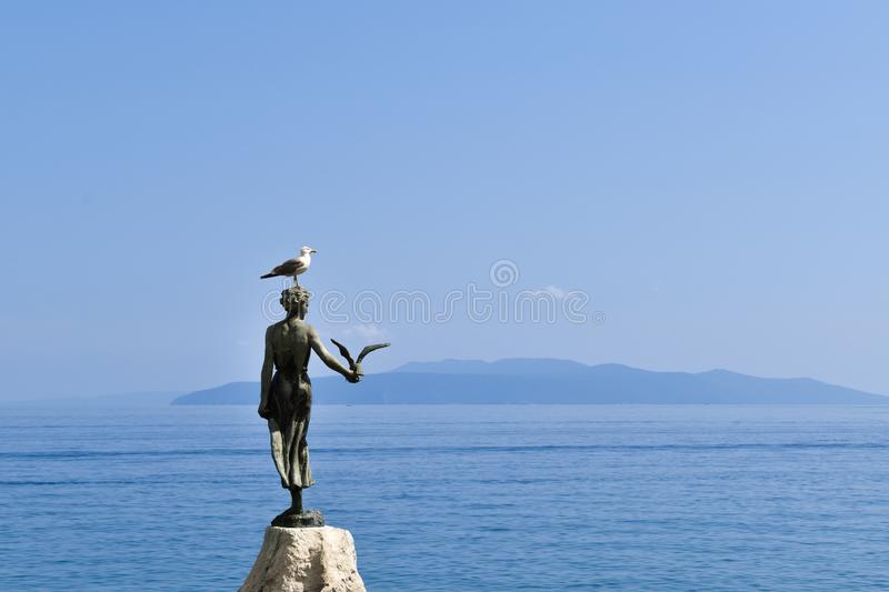 Living seagull standing on top of sculpture named Girl with a seagull royalty free stock photography
