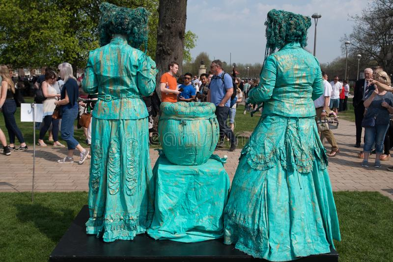 Living statue championship with two green witches and cauldron stock image