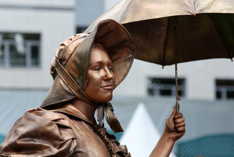 Living statue of a girl dressed in style of 19th century. MOSCOW, RUSSIA - JUN 16, 2012: Living statue of a girl dressed in style of 19th century at the annual stock photography