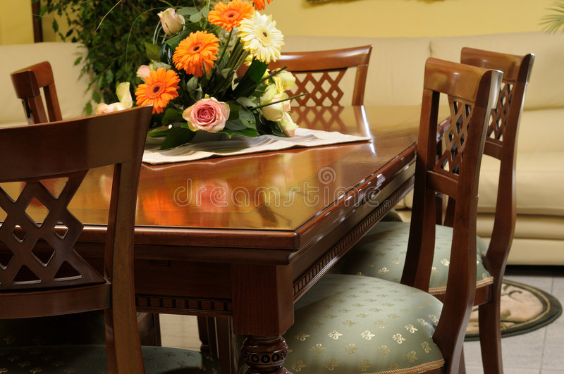 Living table and colored flowers royalty free stock photography
