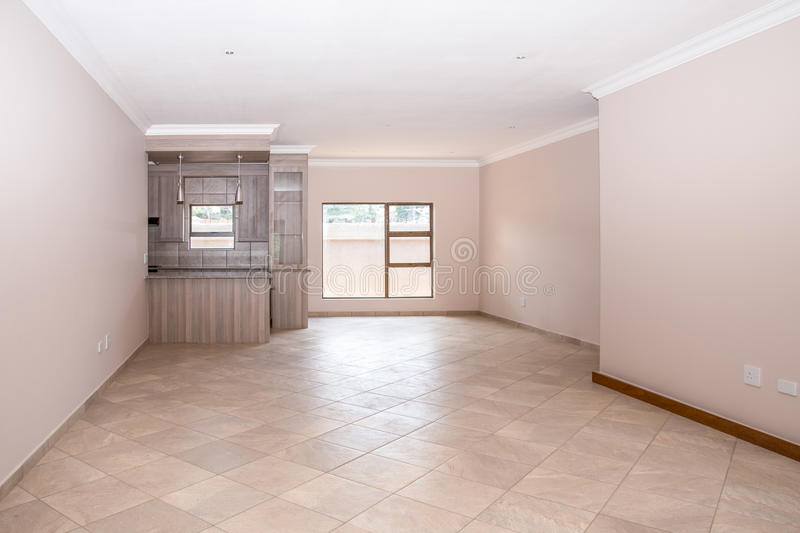 Livingroom of New House. A vacant livingroom of a newly build house, with tiled floors, newly painted walls, and part of the kitchen in the background stock image