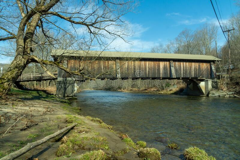 Livingston Manor, NY / United States - April 19, 2020: A side view of the Livingston Manor Covered Bridge spanning the scenic. A side view of the Livingston stock photos