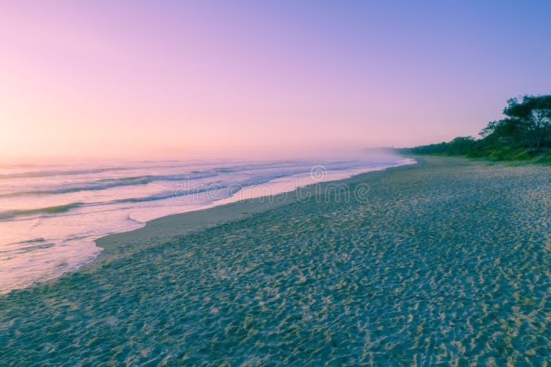 Livlig dimmig solnedgång på den tomma havstranden arkivfoto