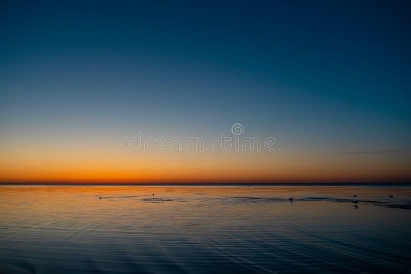 Livlig fantastisk solnedgång i baltiska stater - skymning i havet med horisonten exponerar vid solen royaltyfri fotografi