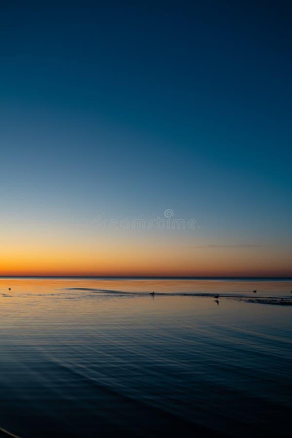 Livlig fantastisk solnedgång i baltiska stater - skymning i havet med horisonten exponerar vid solen arkivbild