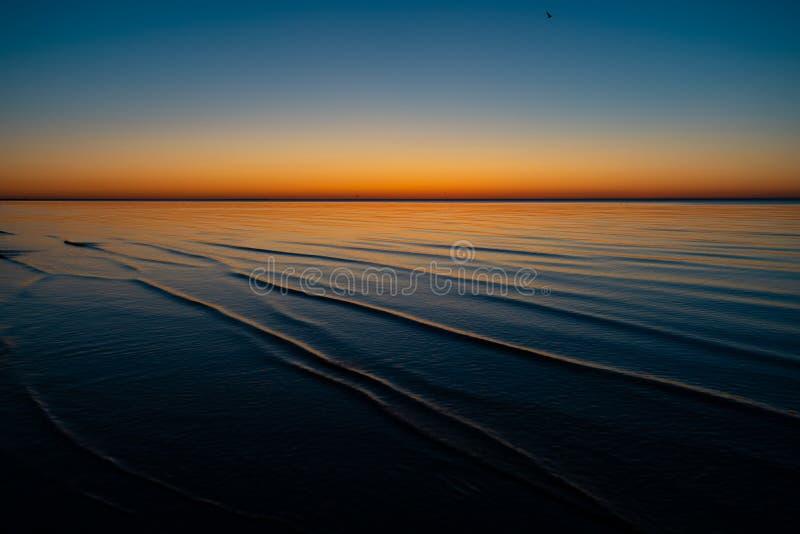 Livlig fantastisk solnedgång i baltiska stater - skymning i havet med horisonten exponerar vid solen royaltyfri foto