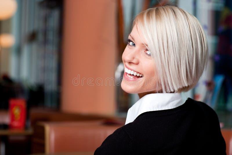 Livlig skratta kvinna i en restaurang royaltyfri fotografi