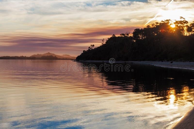Livlig solnedgång, snöig flodbred flodmynning, Victoria, Australien royaltyfri foto