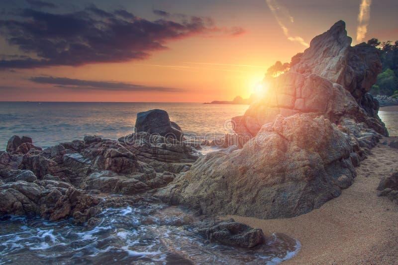 Livlig soluppgång på havet med vaggar och stenar på stranden Vibrerande landskap av havet Seascape av den steniga stranden på gry royaltyfria bilder