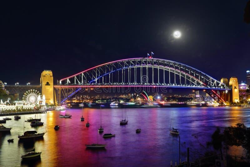 Livliga Sydney Harbour Bridge och stad vid natt royaltyfri foto