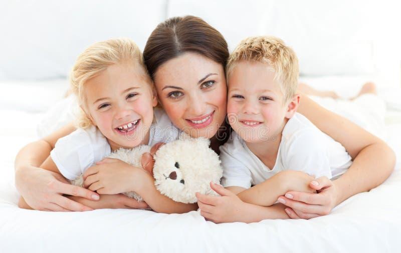 Livligt syskon med deras moder som ligger på ett underlag royaltyfri fotografi