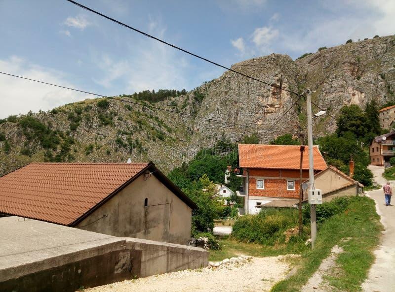 Livno/Bosnien och Hercegovina - Juni 28 2017: En sikt av en typisk gata i Livno Berg, hus och en landsväg royaltyfri foto