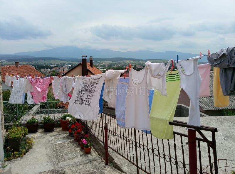 Livno/Bosnien och Hercegovina - Juni 28 2017: Tvätterit torkar på ett rep nära ett hus Panorama av Livno är på bakgrunden royaltyfri foto