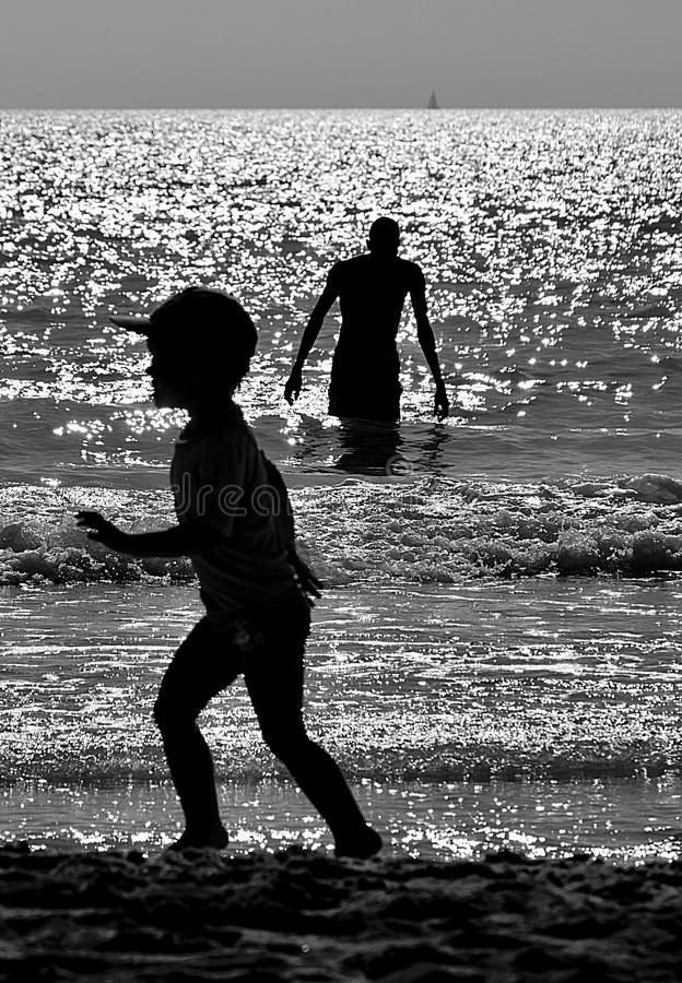 Sea in black and white with people in backlight. stock images