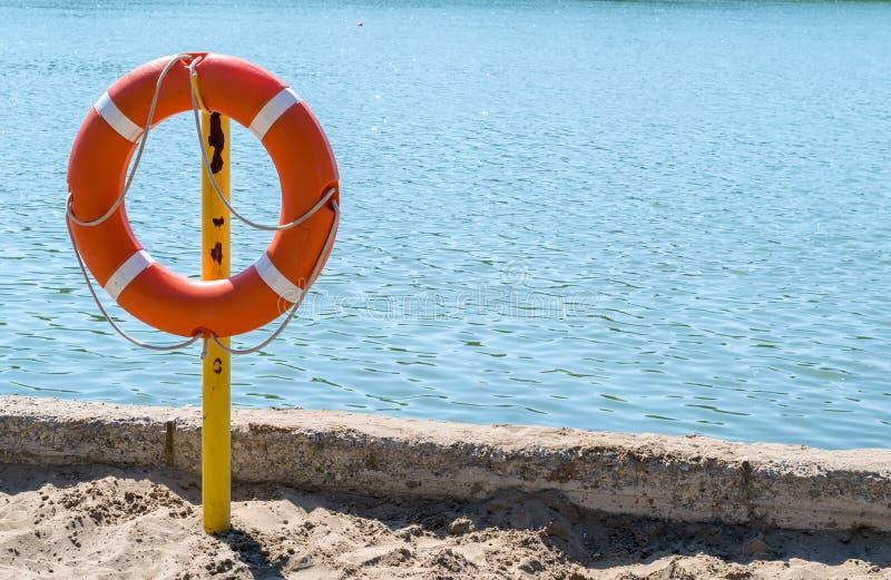 Livpreserver på kusten av sjön som räddar drunkning arkivbilder