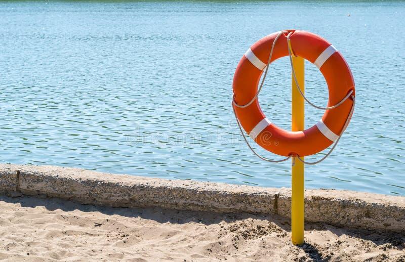 Livpreserver på kusten av sjön som räddar drunkning arkivbild