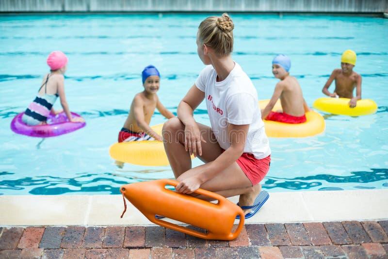 Livräddareinnehavräddningsaktionen kan medan barn som simmar i pöl arkivbild