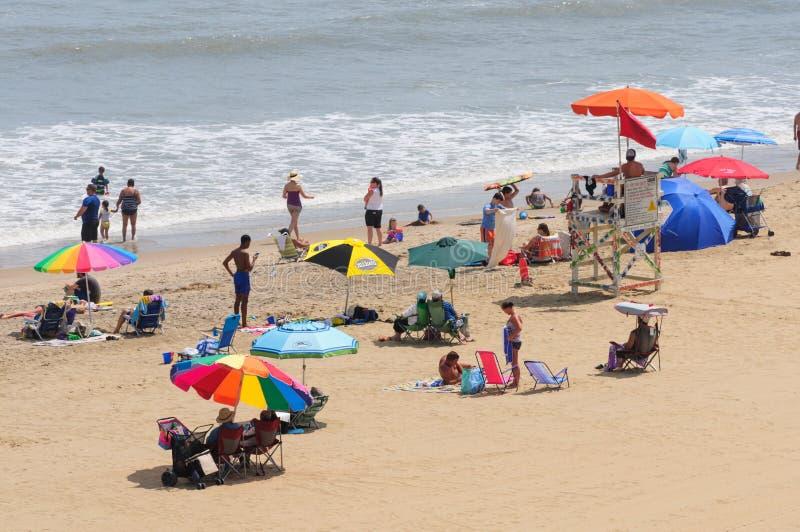 Livräddaren och Sunbathers samlar på sanden på Virginia Beach, VA royaltyfri bild