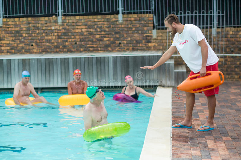 Livräddareportionsimmare på poolsiden arkivfoton