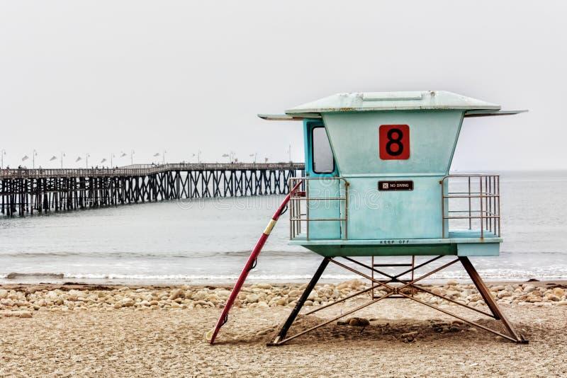 LivräddareStand och surfingbräda på den Ventura pir arkivfoton