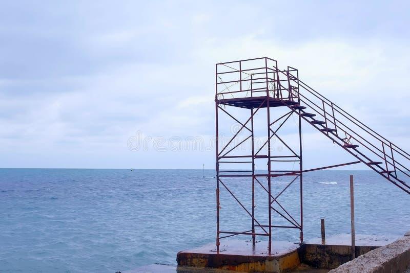 Livräddaretorn på den tomma strandstranden i det lågsäsongt Blåsig dag och stormigt hav royaltyfria foton