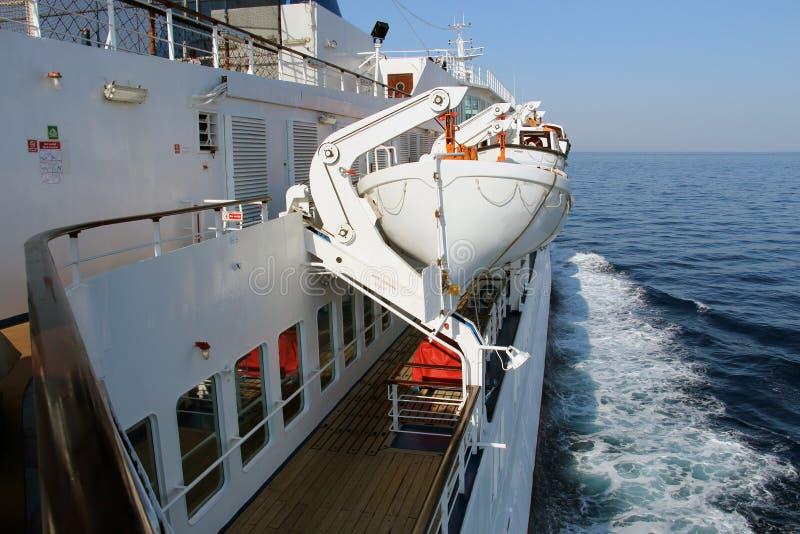 Livräddningsbåtar pryder på ett passagerareskepp i ett hav arkivfoton