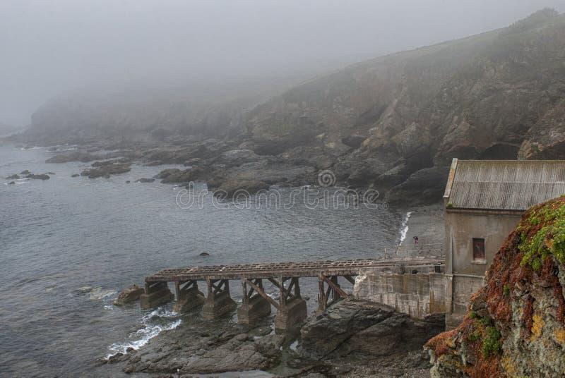 Livräddningsbåtstation inom den Polpeor lilla viken, ödla, Cornwall UK arkivbilder