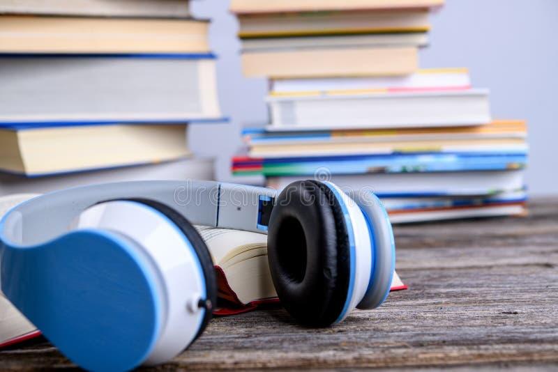 Livre avec casque devant des piles de livres différents images stock