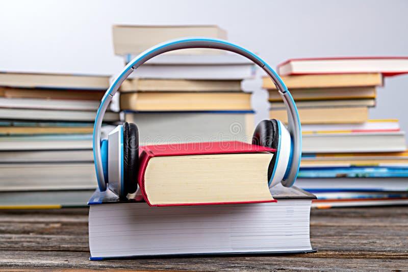 Livre avec casque devant des piles de livres différents photographie stock libre de droits