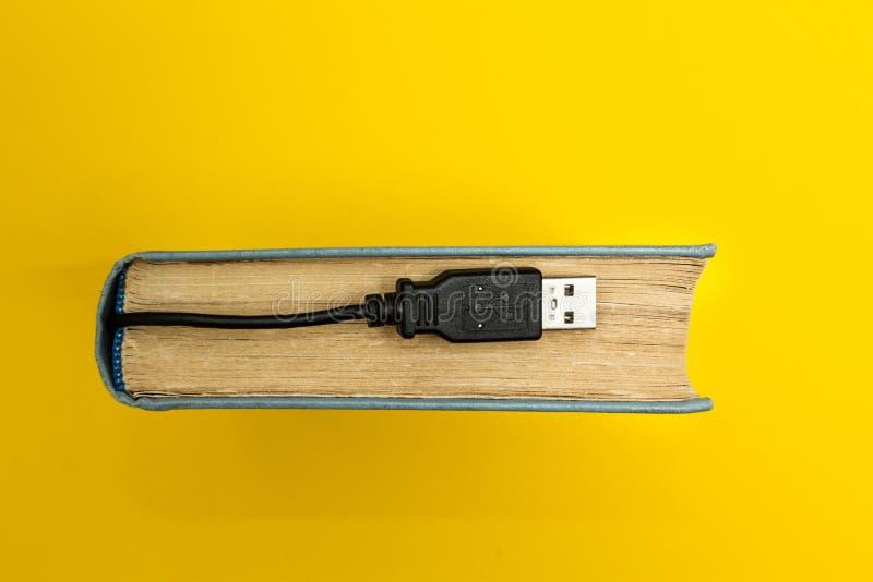 Livre avec un connecteur pour la connexion à un ordinateur sur un fond jaune illustration stock