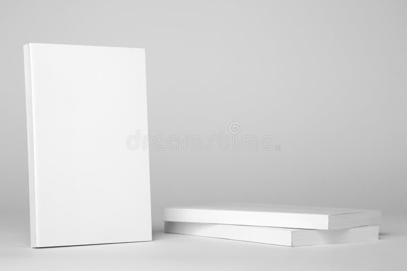 Livre blanc de vrai livre broché à côté d'une pile de livres sur un fond gris image libre de droits