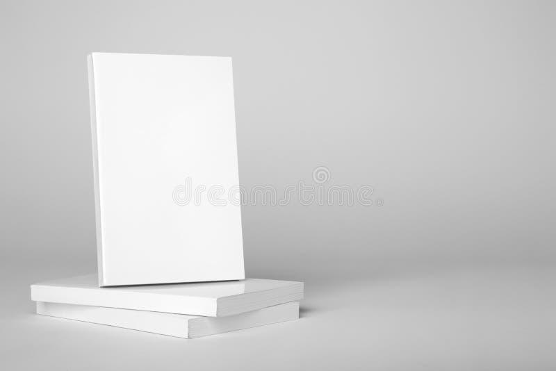 Livre blanc de vrai livre broché au-dessus d'une pile de livres sur un fond gris photo libre de droits